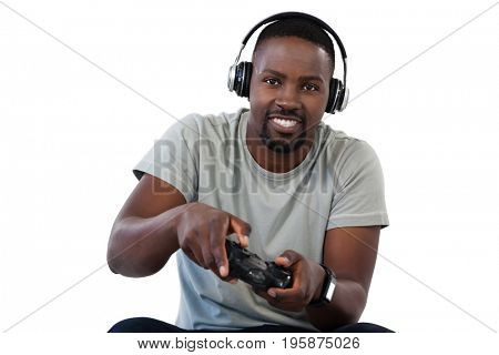 Portrait of smiling man playing video game against white background