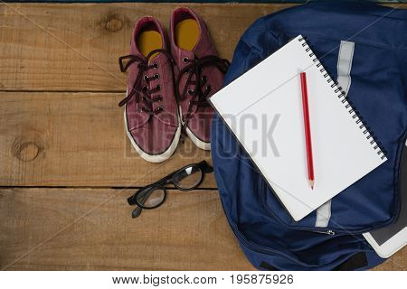 Close-up of shoes, spectacles, book, pencil, digital tablet and schoolbag on wooden table