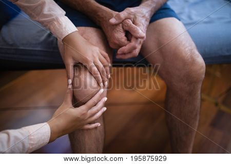 High angle view of female therapist examining knee while senior male patient sitting on bed at hospital ward