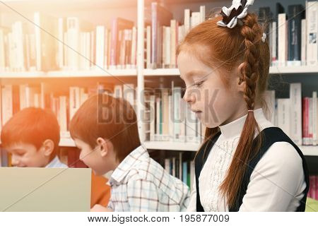 Little girl with classmates at school library