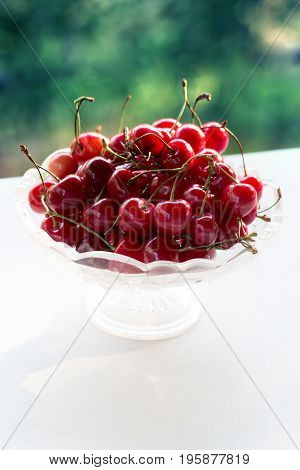 Cherries in a glass bowl on a wooden table. Ripe juicy red cherry