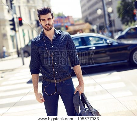 Casual young man walking in the city, holding bag, listening to music.