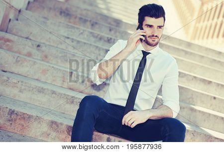 Handsome young man talking on mobilephone, sitting on stairs outdoors.