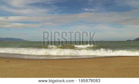 Marine waves hurry ashore, struck at off-shore stone, and washing off sand at-sea.