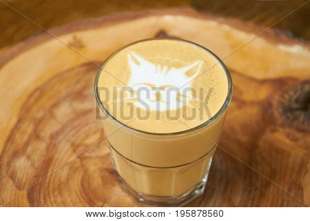 Latte glass with cat art. Coffee foam and blurred background. Cute and tasty.