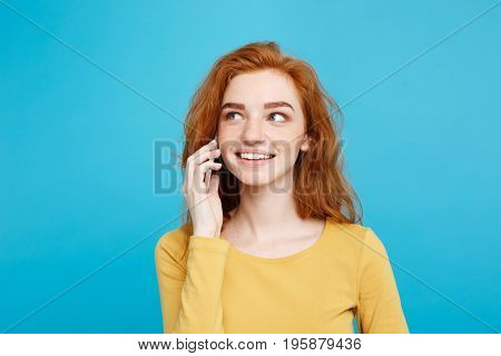 Lifestyle and Technology concept - Portrait of cheerful happy ginger red hair girl with joyful and exciting talking with friend by mobile phone. Isolated on Blue Pastel Background. Copy space.
