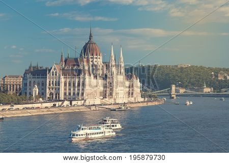Travel and european tourism concept. Parliament and riverside in Budapest Hungary with sightseeing ships during summer day. Toned image.