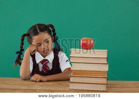 Unhappy schoolgirl looking at books stack and apple against chalkboard in classroom