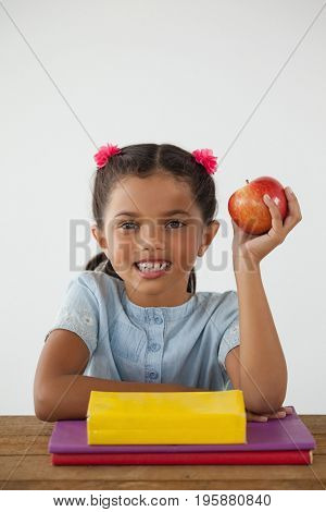 Adorable schoolgirl holding a red apple against white background
