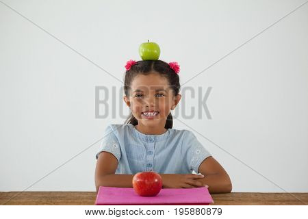 Portrait of schoolgirl sitting with green apple on her head against white background
