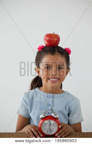 Schoolgirl sitting with apple on her head and alarm clock against white background