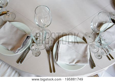 Serving festive dining event with glasses and plates for consumers - the top view. Cutlery for people in the restaurant.