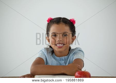 Portrait of young girl sitting on her desk