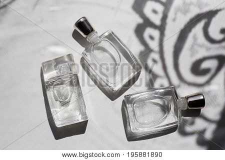 Three small bottles of perfume in grey background
