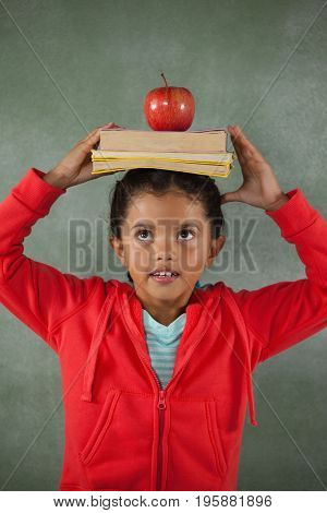 Young girl balancing books and apple on her head against chalk board