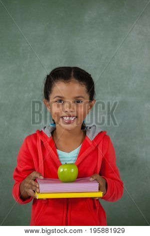 Portrait of young girl holding apple and books