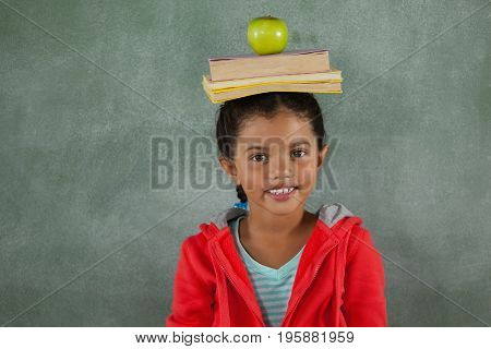 Portrait of young girl balancing books and apple on her head