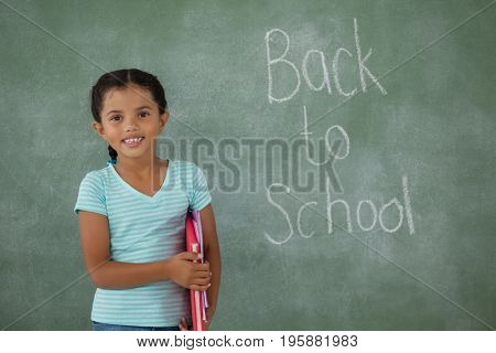 Young girl holding books against chalk board