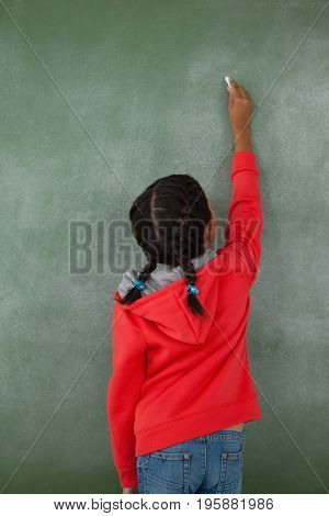 Rear view of young girl writing on chalk board