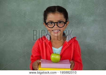 Portrait of young girl in glasses holding apple and books