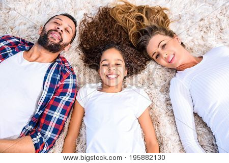 Young parents and their daughter laying on the carpet