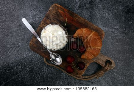 Iced Coffee With Whipped Cream In Tall Glass And Fresh Croissant And Cherries