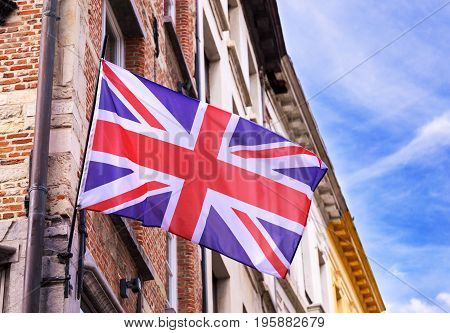 Great Britain flag on brick wall of old building on sunny day. With copy space