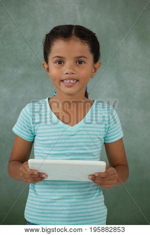 Young girl holding digital tablet against chalk board
