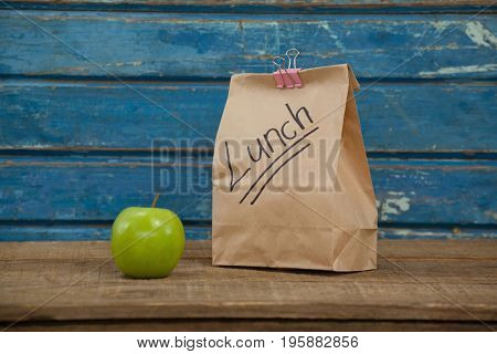 Apple and lunch bag against blue wooden background