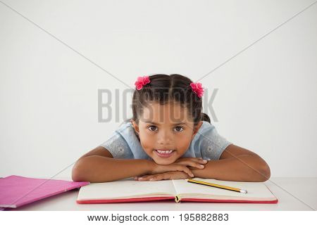 Portrait of young girl with her head on desk against white background