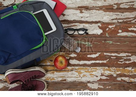 Bagpack, water bottle, apple, digital tablet, shoes and spectacle on wooden background