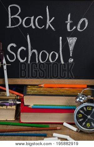 Alarm clock, pencils, chalk, books and slate with back to school text against blue wooden background