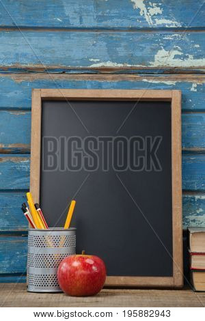 Stack of books, slate, apple and pen holder against blue wooden background