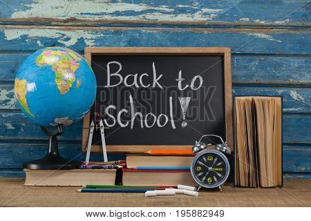 Globe, alarm clock, pencils, chalk, books and slate with back to school text against blue wooden background