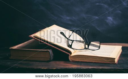 Old Book And Eye Glasses On Blackboard Background