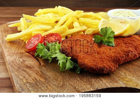 Wiener Schnitzel And French Fries Served With Sauces And Salad On Rustic Wooden Table