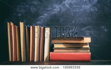 Old Books And Eye Glasses On Blackboard Background