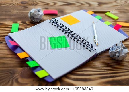 Open notepad with office supplies. Open notepad lies on a wooden desktop with marker, pencil, pen and Stickers