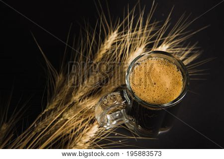 Wheat spikelets with one mug of beer on empty black background. Ripe ears of wheat barley with beer glass. Top view.