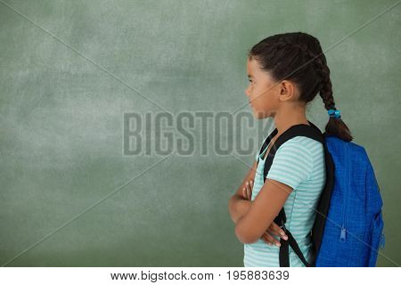 Side view of young girl with her arms crossed against chalk board
