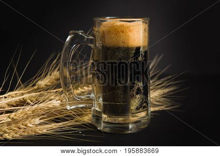 Beer mug on a black background. Ripe ears of wheat barley with beer glass.