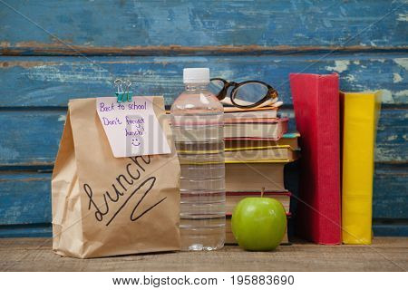 Stack of books, apple, water bottle, spectacles and lunch bag against blue wooden background
