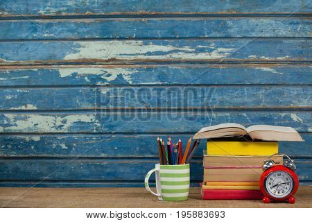 Stack of books, alarm clock and pen holder against blue wooden background