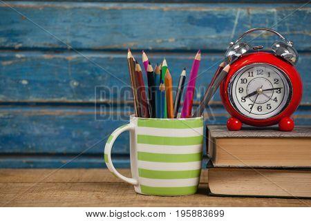Alarm clock, books and pen holder against blue wooden background