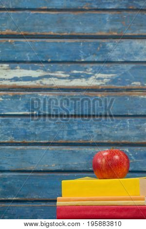 Stack of books and apple against blue wooden background