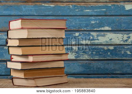 Stack of books against blue wooden background