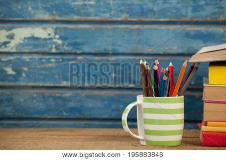 Close-up of pen holder against blue wooden background