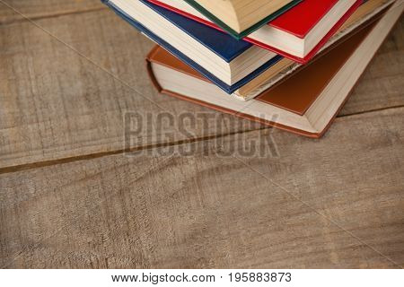 Top view of stack of books on wooden background