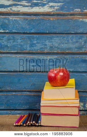Stack of books, apple and color pencils against blue wooden background