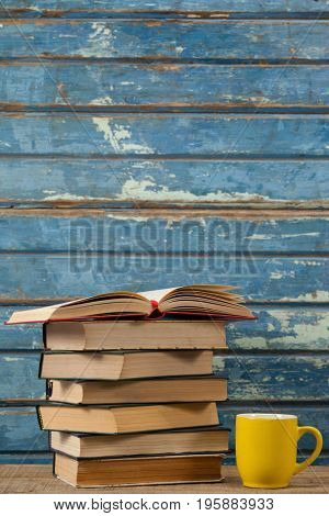 Stack of books and coffee cup against blue wooden background